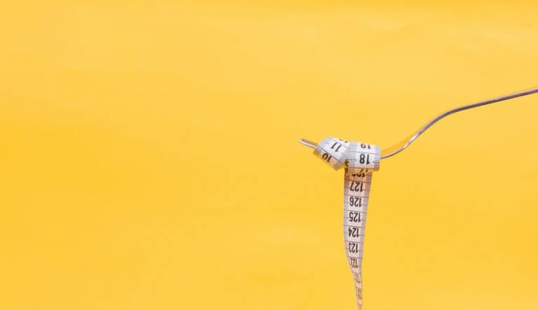 white measuring tape wrapped around a fork with a yellow background.