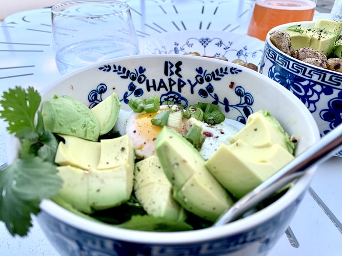an avocado bowl with egg and greens