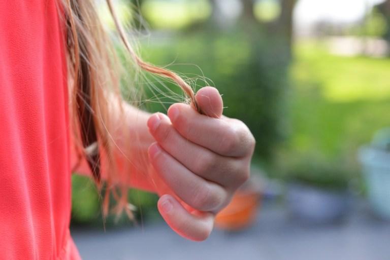 A girl holding her weak, brittle hair
